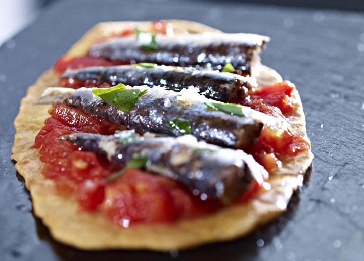 Coca de sardinas con tomates y albahaca